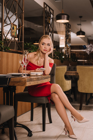 attractive woman in red dress sitting in restaurant, using smartphone and waiting for man Imagens