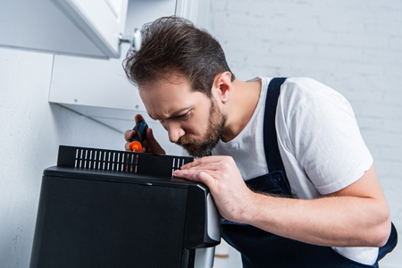 focused handyman in working overall repairing coffee machine by screwdriver in kitchen Reklamní fotografie