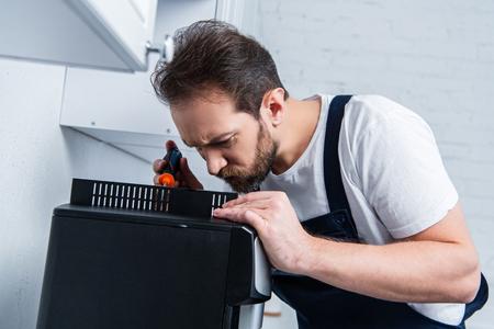focused handyman in working overall repairing coffee machine by screwdriver in kitchen Reklamní fotografie - 118430947