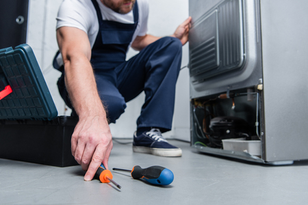 cropped shot of repairman in working overall taking screwdriver from floor near broken refrigerator in kitchen Banque d'images - 118430987