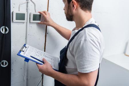 Erwachsener bärtiger Elektriker mit Klemmbrett, der die Schalttafel überprüft