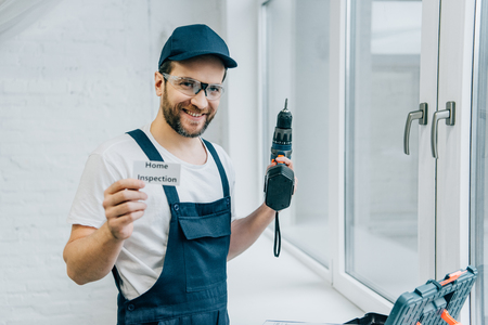 happy adult male craftsman holding electric drill and showing card with lettering home inspection Stok Fotoğraf