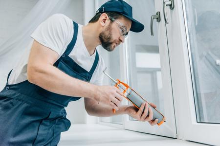 bearded adult repairman fixing window with sealant gun 스톡 콘텐츠