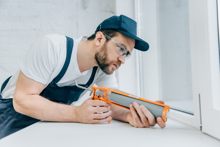 concentrated adult repairman fixing window with sealant gun