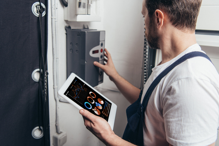 male electrician holding digital tablet with graphs on screen and checking electric box Reklamní fotografie