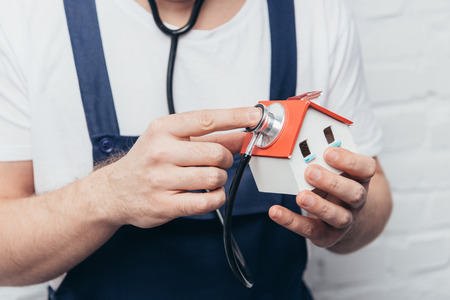 cropped shot of craftsman checking house figure by stethoscope, home inspection concept