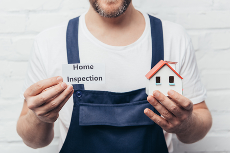 cropped image of male craftsman showing house model and card with lettering home inspection Banque d'images