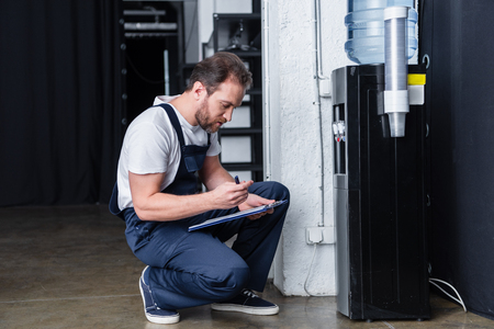 side view of male repairman writing in clipboard during checking of broken water cooler Reklamní fotografie
