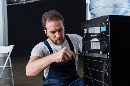 bearded male craftsman repairing water cooler with screwdriver