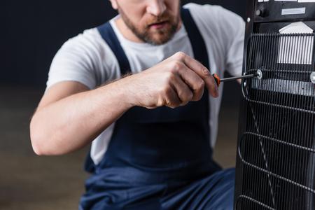 cropped shot of male craftsman repairing water cooler with screwdriver 版權商用圖片