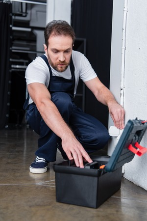 electrician in working overall taking tools from toolbox during repairing of plug socket