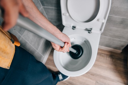cropped shot of male plumber using plunger and cleaning toilet in bathroom Фото со стока