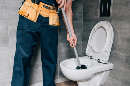 partial view of male plumber using plunger and cleaning toilet in bathroom