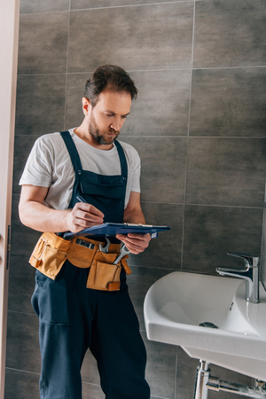 handsome male plumber with toolbelt writing in clipboard near broken sink in bathroom