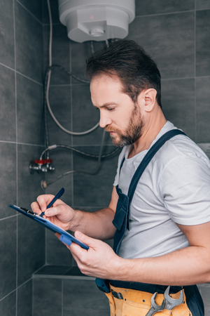 adult male plumber writing in clipboard and checking electric boiler in bathroom