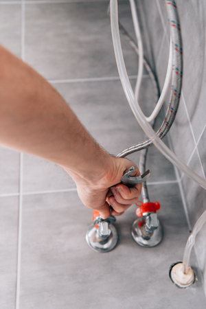 cropped image of male plumber repairing electric boiler by wrench in bathroom