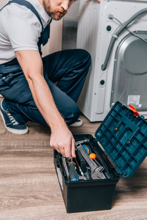 cropped shot of craftsman taking tools from toolbox while repairing washing machine in bathroom