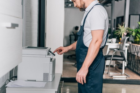 cropped image of male handyman repairing copy machine in modern office