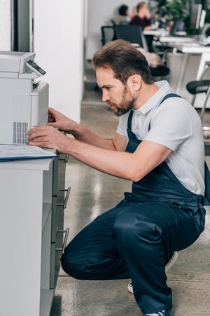 side view of male handyman repairing copy machine in modern office