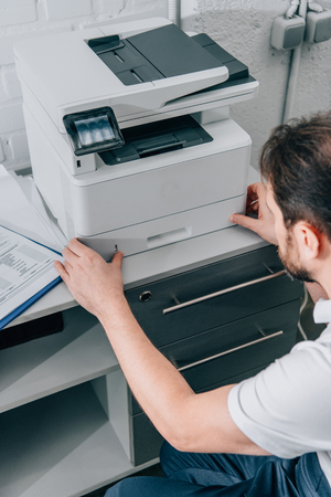 high angle view of male handyman repairing copy machine in modern office