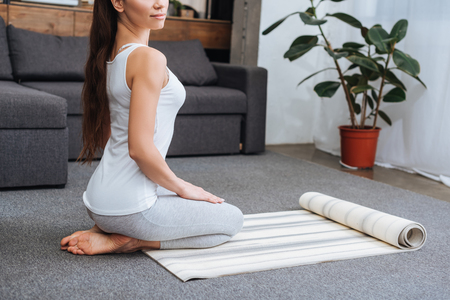 cropped view of woman sitting on fitness mat and practicing hero pose at home Stockfoto