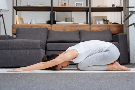 woman practicing balasana at home in living room