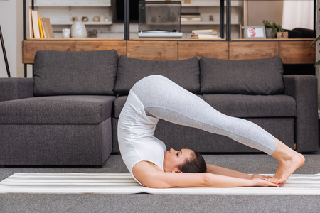 woman practicing boat pose at home in living room