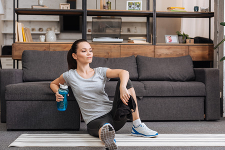sportswoman with towel and sport bottle sitting in living room