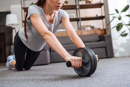 cropped view of sportswoman training with ab wheel at home