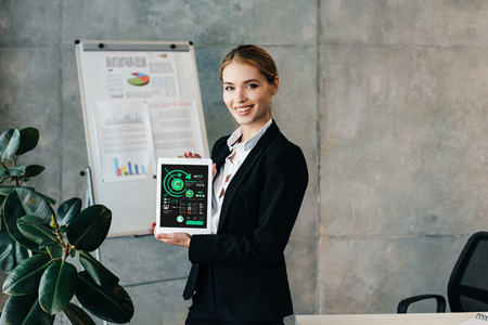 Pretty smiling businesswoman holding digital tablet with inphographics on screen 写真素材