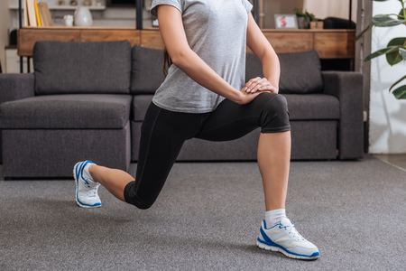cropped view of sportswoman doing lunge exercise at home