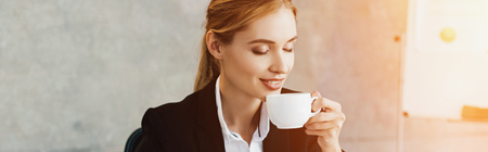 Charming businesswoman enjoys drinking coffee with closed eyes 스톡 콘텐츠