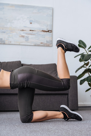 cropped view of sportswoman doing donkey kick exercise at home Stock Photo