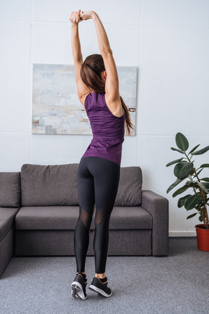 back view of young sportswoman stretching before workout at home