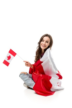 beautiful smiling woman covered in canadian flag holding maple leaf flag isolated on white