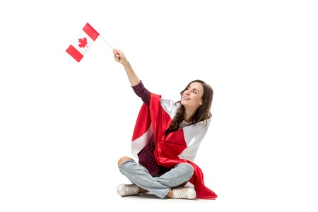 woman covered in canadian flag waving with maple leaf flag isolated on white Stock Photo