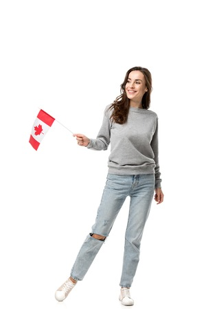 beautiful smiling woman in grey casual clothes holding canadian flag isolated on white