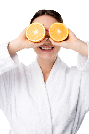 smiling woman in white bathrobe holding oranges in front of face isolated on white