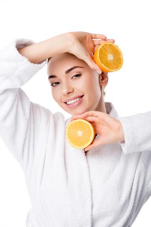 beautiful smiling woman in white bathrobe holding oranges isolated on white