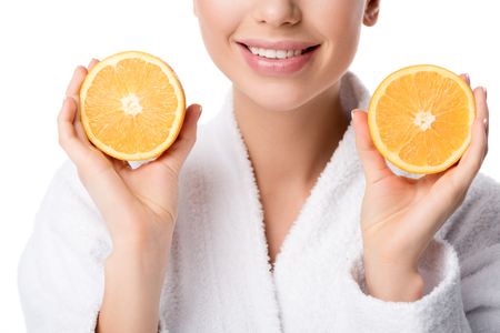 partial view of smiling woman in white bathrobe holding oranges isolated on white