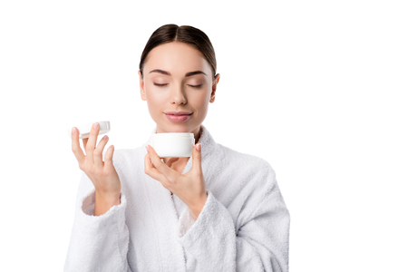 woman in bathrobe with eyes closed smelling aroma of face cream isolated on white Stok Fotoğraf