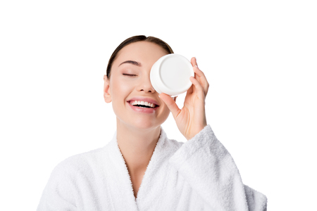 cheerful woman in bathrobe holding moisturizing cream in front of face isolated on white Standard-Bild