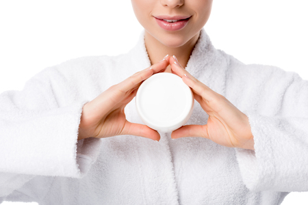 partial view of woman in bathrobe holding face cream isolated on white