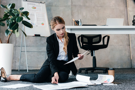 barefoot businesswoman sitting on floor and reading document