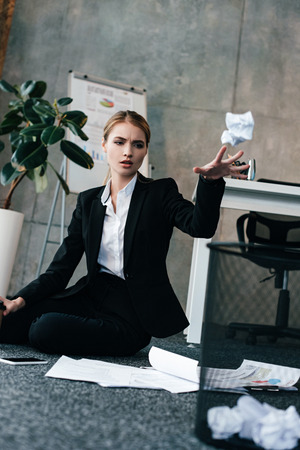 businesswoman sitting on floor and throwing napkin to basket