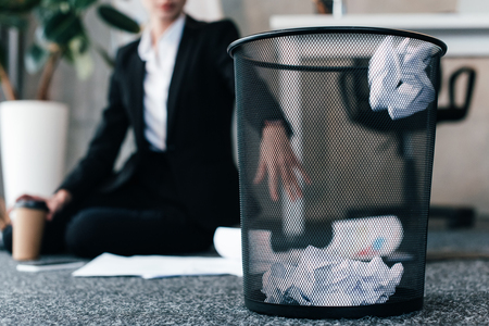 selective focus of crumpled paper in basket while businesswoman sitting on floor