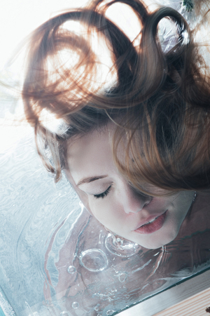 close up of beautiful girl posing underwater with closed eyes