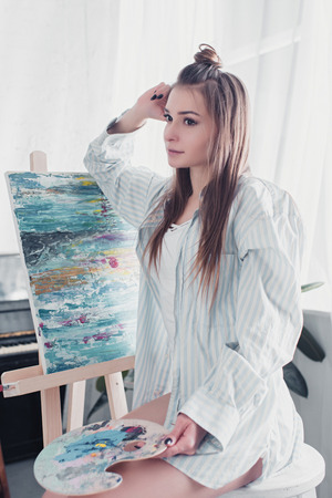 thoughtful artist sitting on chair in front of easel and holding palette at home