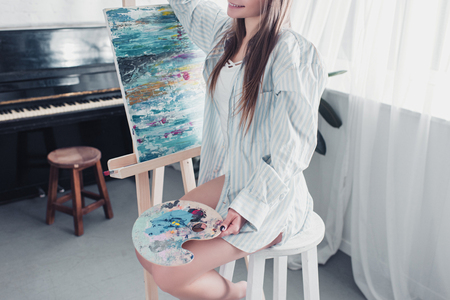 cropped view of artist sitting on chair in front of easel and holding palette in living room Stock Photo