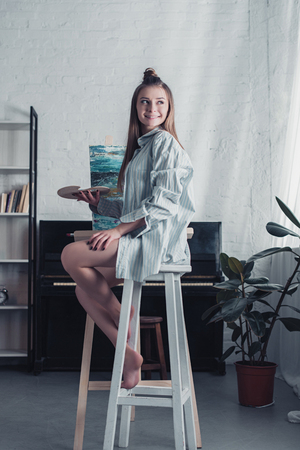 smiling artist sitting on highchair in front of easel and holding palette at home